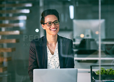 Buy stock photo Shot of a confident businesswoman working on a laptop in an office at night