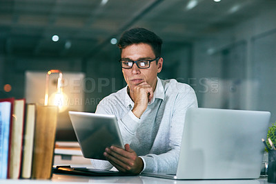 Buy stock photo Shot of a handsome young businessman using a digital tablet in an office at night