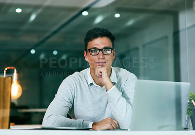 Buy stock photo Portrait of a confident young businessman working in an office at night