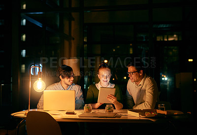 Buy stock photo Shot of businesspeople working together on a digital tablet in an office at night