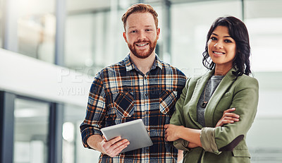 Buy stock photo Portrait of two confident young coworkers working together in a modern office