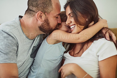 Buy stock photo Shot of a mother and father bonding with their adorable young daughter at home