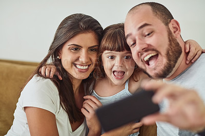 Buy stock photo Shot of a mother and father taking selfies together with their young daughter at home