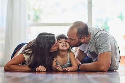 Buy stock photo Portrait of a mother and father bonding with their adorable young daughter at home