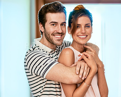 Buy stock photo Portrait of a cheerful young couple holding each other while looking at the camera and standing inside at home during the day
