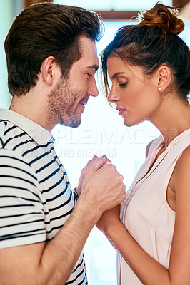 Buy stock photo Shot of a cheerful young couple holding each other's hands while standing face to face inside at home during the day