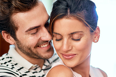 Buy stock photo Shot of a cheerful young couple holding each other while looking at the camera and standing inside at home during the day
