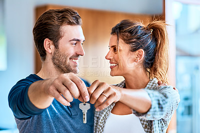 Buy stock photo Shot of a cheerful young couple holding a key together to their new home while standing inside during the day