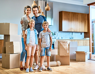 Buy stock photo Portrait of a cheerful young family standing together in their new home inside during the day
