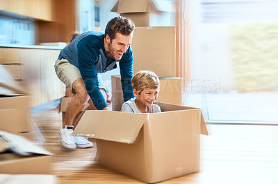 Buy stock photo Shot of a cheerful young man pushing his son around in a box imagining its a car inside at home during the day