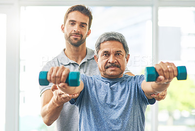 Buy stock photo Cropped portrait of a young male physiotherapist assisting a senior patient in recovery