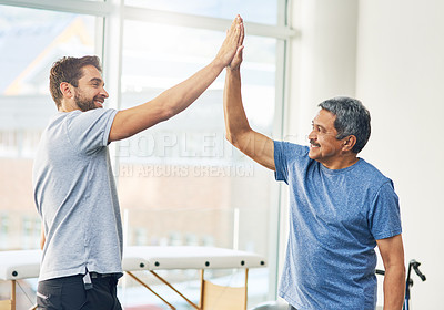Buy stock photo Cropped shot of a young male physiotherapist and his senior patient high fiving after a great session