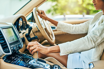 Buy stock photo Shot of an unrecognizable businesswoman driving in a car and changing gears while going to work during the day