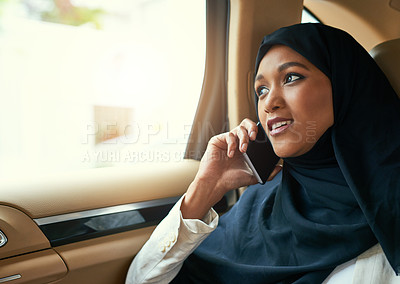 Buy stock photo Shot of a cheerful young businesswoman talking on her mobile phone while being seated in the back of a car on her way to work