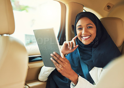 Buy stock photo Portrait of a cheerful young businesswoman browsing on a digital tablet while seated in the backseat of a car driving to work during the day