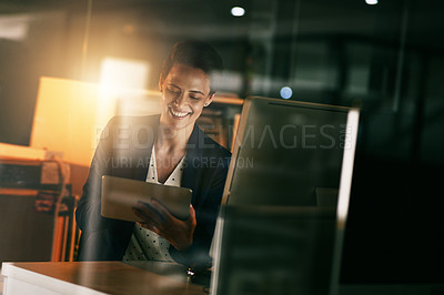 Buy stock photo Shot of a young businesswoman working late on a digital tablet in an office
