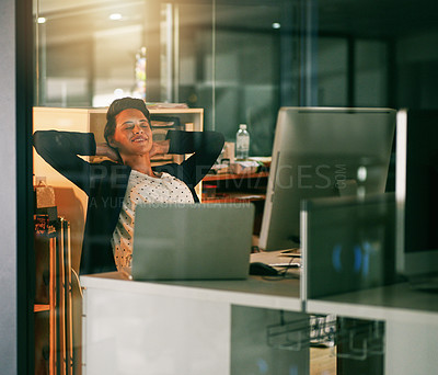 Buy stock photo Shot of a young businesswoman taking a break while working late in an office