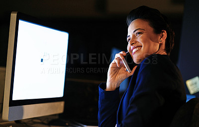 Buy stock photo Shot of a young businesswoman talking on a cellphone while working late in an office