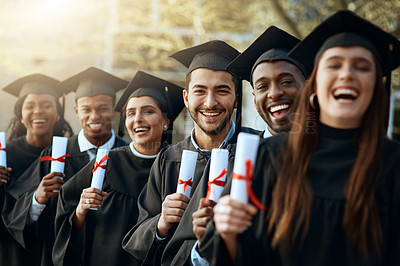 Buy stock photo Portrait of a group of young students holding their diplomas on graduation day