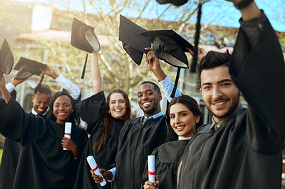 Buy stock photo Portrait of a group of happy young students taking their hats off on graduation day