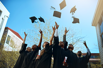 Buy stock photo Shot of a group of young students throwing their hats in the air on graduation day