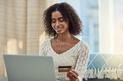 Buy stock photo Shot of an attractive young woman making payments online with a credit card at home