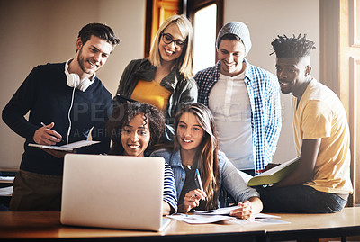 Buy stock photo Cropped shot of a group of university students working on an assignment together in class