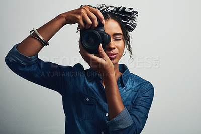 Buy stock photo Studio shot of an attractive young woman taking a picture with a dslr camera against a grey background