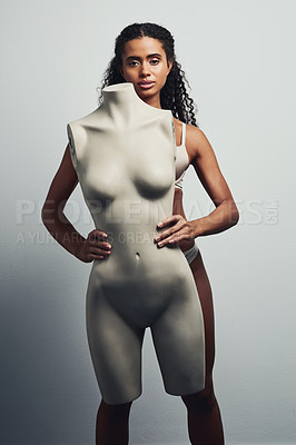 Buy stock photo Studio shot of an attractive young woman posing with a mannequin against a grey background