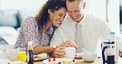 Buy stock photo Shot of an affectionate middle aged couple having breakfast together in the morning at home