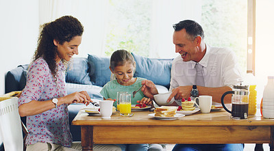 Buy stock photo Shot of a cute little girl having breakfast with her parents in the morning at home
