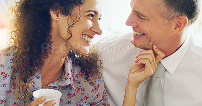 Buy stock photo Shot of an affectionate middle aged couple having coffee together in the morning at home