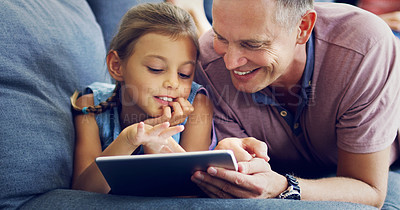 Buy stock photo Shot of a cute little girl using a digital tablet with her father on the sofa at home