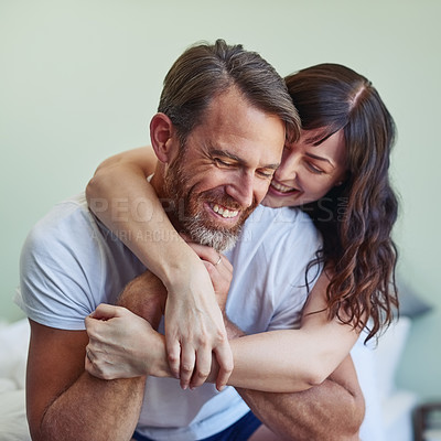 Buy stock photo Shot of a cheerful young couple embracing each other with a hug while relaxing on the bed at home during morning hours