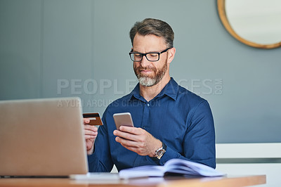 Buy stock photo Shot of a cheerful middle aged businessman working on his laptop and paying bills with his credit card at home during the day