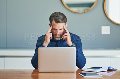 Buy stock photo Shot of a stressed out middle aged businessman working on his laptop while trying to think at home during the day