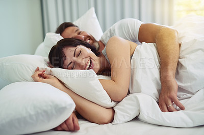 Buy stock photo Shot of a relaxed young couple trying sleeping in each other's arms in bed during morning hours