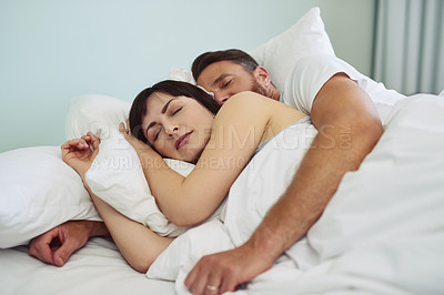 Buy stock photo Shot of a relaxed young couple sleeping in each other's arms in bed during morning hours