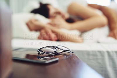 Buy stock photo Shot of a pair of glasses and a cellphone standing next to each other on a bedside table at home during the day