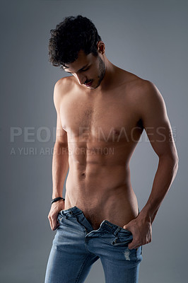 Buy stock photo Studio shot of a handsome young shirtless man undressing against a grey background