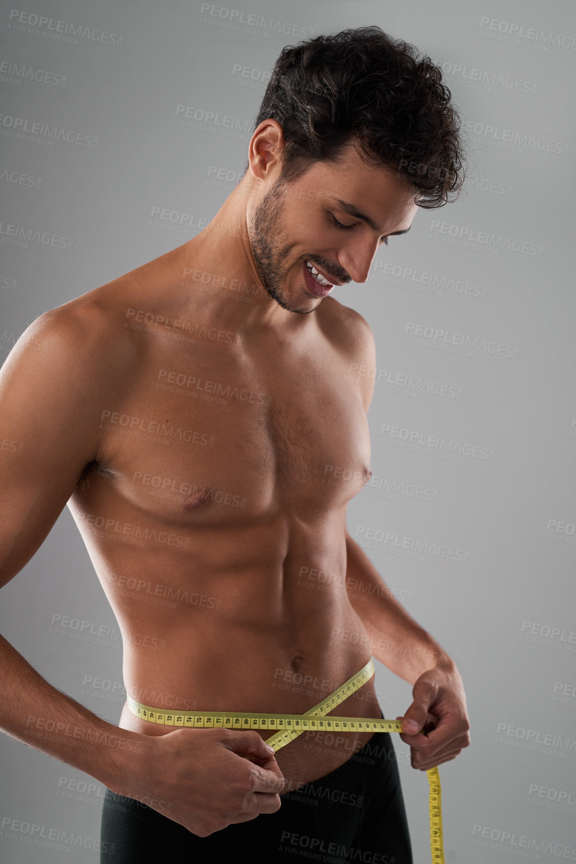 Buy stock photo Studio shot of a handsome young shirtless man measuring his midsection against a grey background