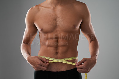 Buy stock photo Studio shot of an unrecognizable shirtless man measuring his midsection against a grey background