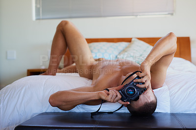 Buy stock photo Shot of a handsome shirtless young man taking a picture on his bed at home