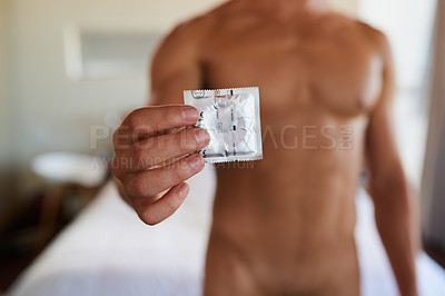 Buy stock photo Cropped shot of an unrecognizable shirtless man holding a condom at home