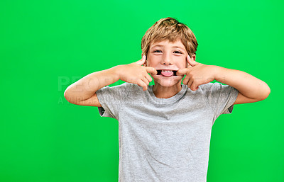 Buy stock photo Studio portrait of a young boy making a funny face against a green background