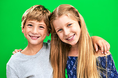 Buy stock photo Studio portrait of two adorable young children standing against a green background