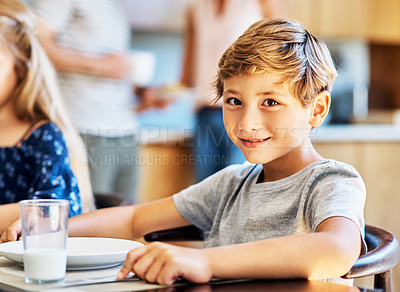 Buy stock photo Portrait of a young boy sitting at the breakfast table at home