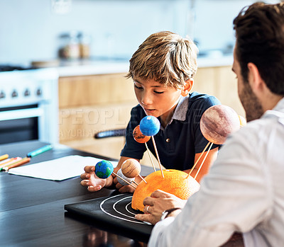 Buy stock photo Shot of a father helping his little son with a school project at home