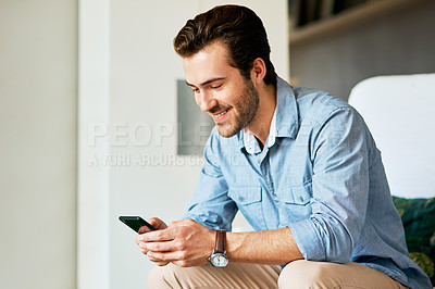 Buy stock photo Shot of a handsome young man texting on a cellphone at home