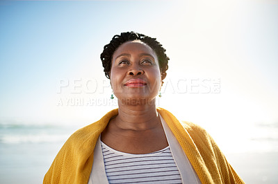 Buy stock photo Shot of a mature woman enjoying a day at the beach